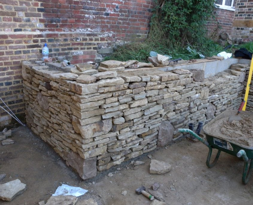 Building a wall during a garden project management job