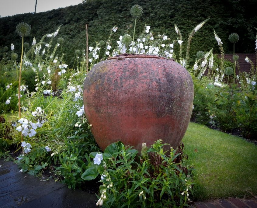 photo of english garden with monochrome white planting and rustic containers in sussex